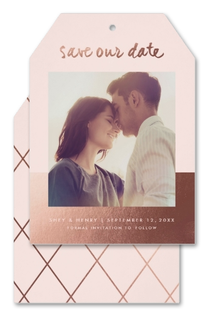Photo save the date cards die-cut into a sweet tag shape. Featuring soft pink complemented by rose gold. The front features a photo of the couple and the back a chic diamond pattern.